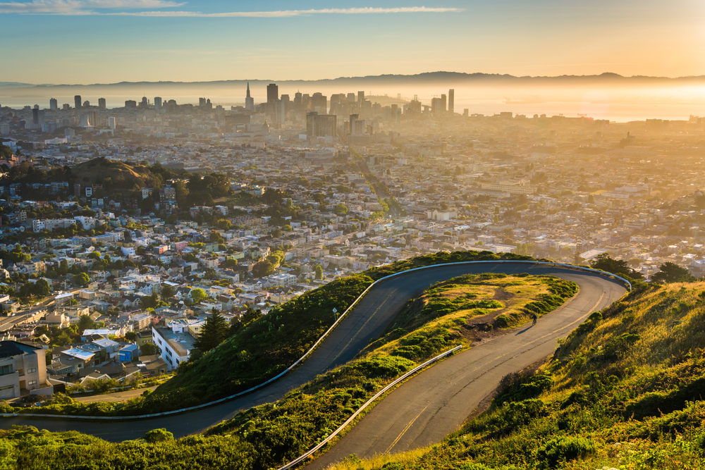Curvy road and view of downtown at sunrise from Twin Peaks, in San Francisco, California.