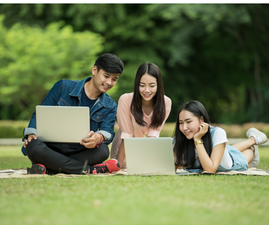 Students on lawns looking at laptops-1